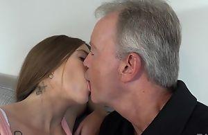 Sex-starved brunette pleasuring old challenge on someone's skin sofa